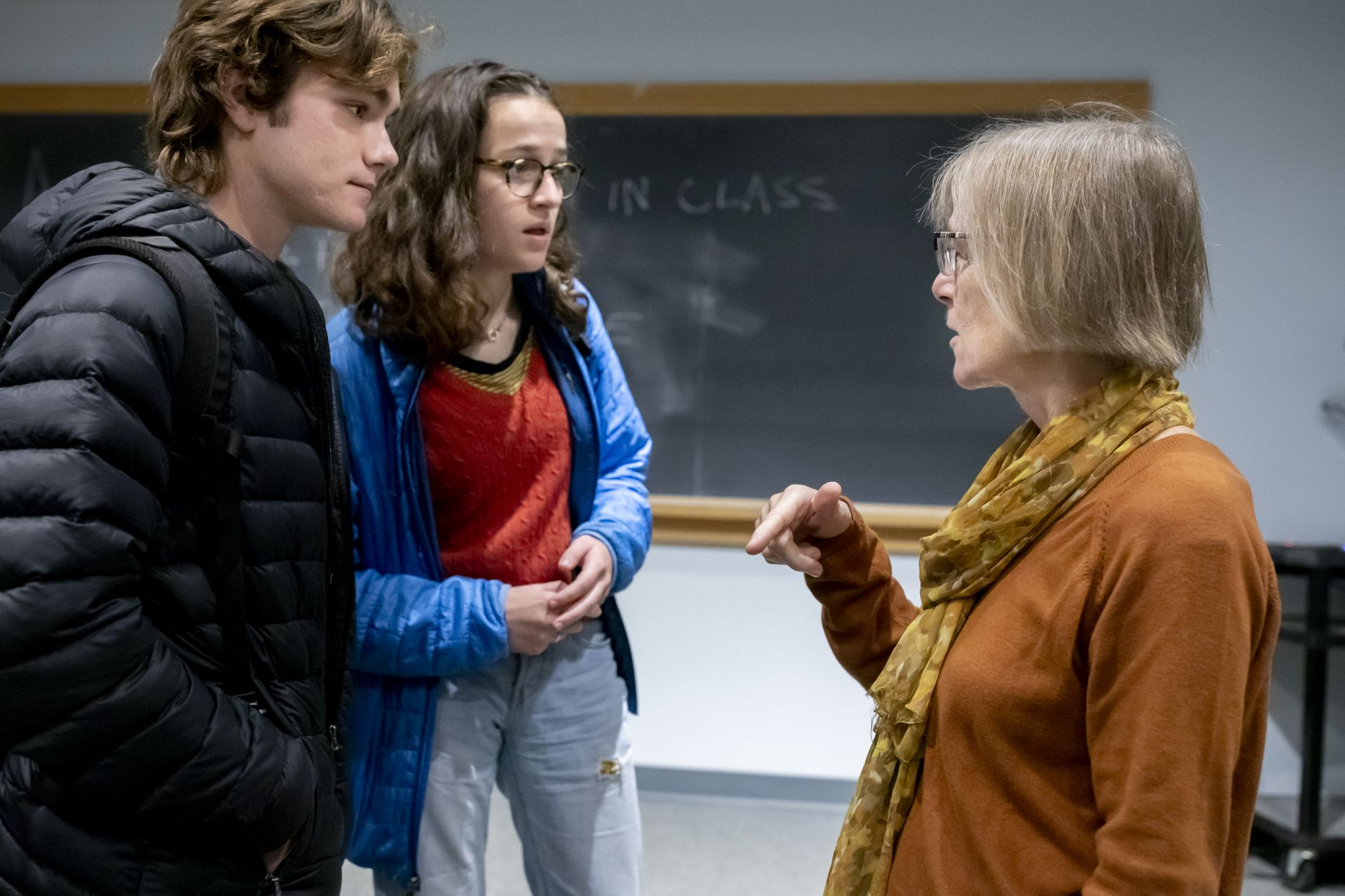"Jasper Beardslee '22 of Miami and Elly Beckerman '22 of Washington, D.C., students in Costlow's ""Lives in Place"" course, wedge in a quick conversation with her after class. (Phyllis Graber Jensen/Bates College)"