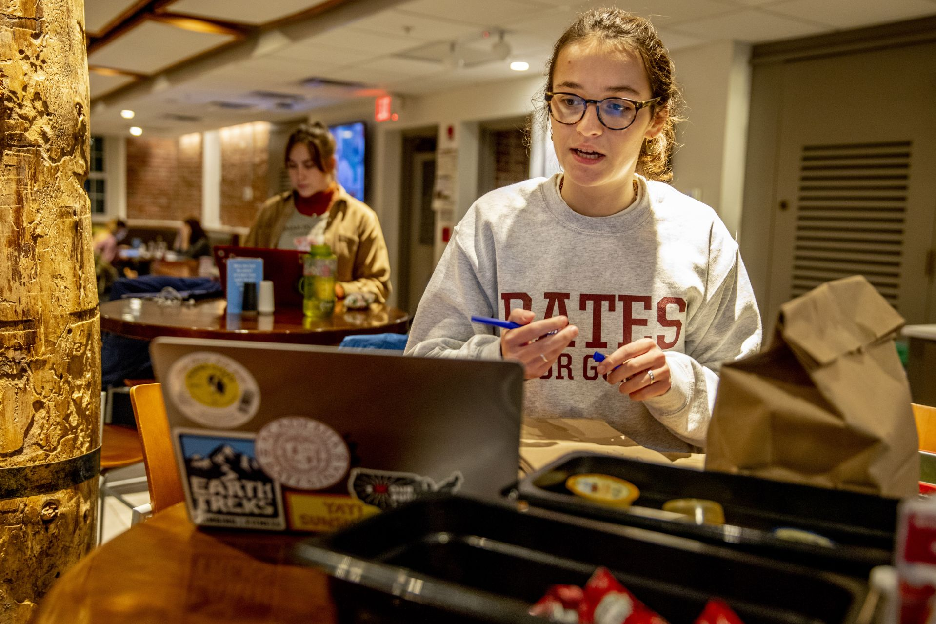 Bates Den Deliver Service in operation between 9-10 p.m. on Tuesday, Nov. 19, 2019. Serving as the CEO this year is Grace Warder '20 of NYC, and taking the orders and making the deliveries tonight are Olivia Kranefuss '22 of Madison, N.J.,in the corduroy shirt and Elly Beckerman '22 of Washington, D.C., in glasses. All three women are environmental studies majors. Roman Hudgins of Dining Services is shown handing over an order to Kranefuss who bikes to her fist delivery at Parker, passing through the Library Quad, both on the Quad and the Library Well. Beckerman makes a delivery to Frye Street and bikes across the Historic Quad to get there. And Harley Rinehart, in gray shirt and garnet hat takes the order from Kranefuss after she waits in line to place it.