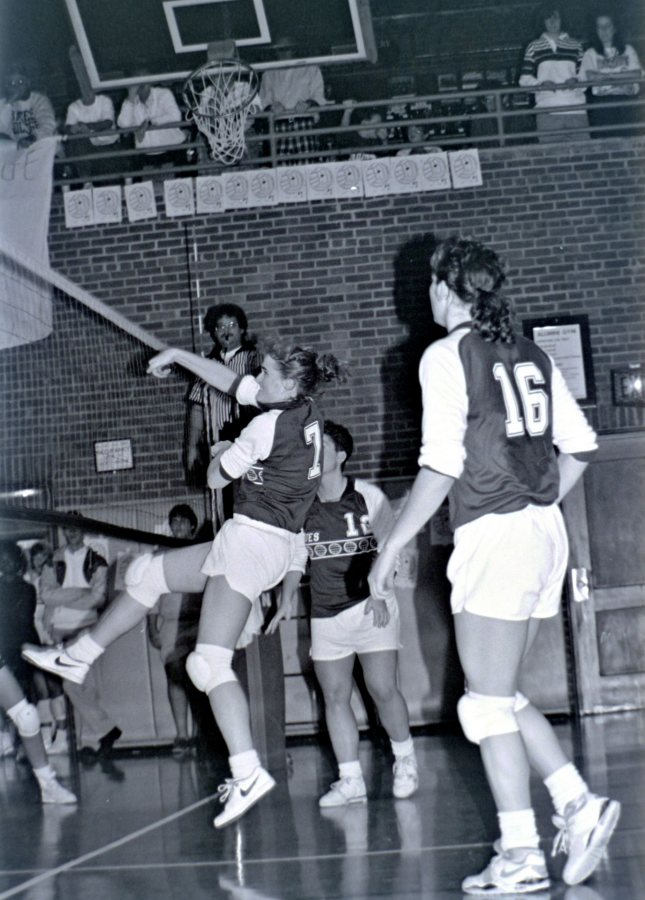 Julie Roche Simplicio '91 spikes the ball while All-American Rachel Clayton '90 (No. 16) looks on. (Scott Pim '93)