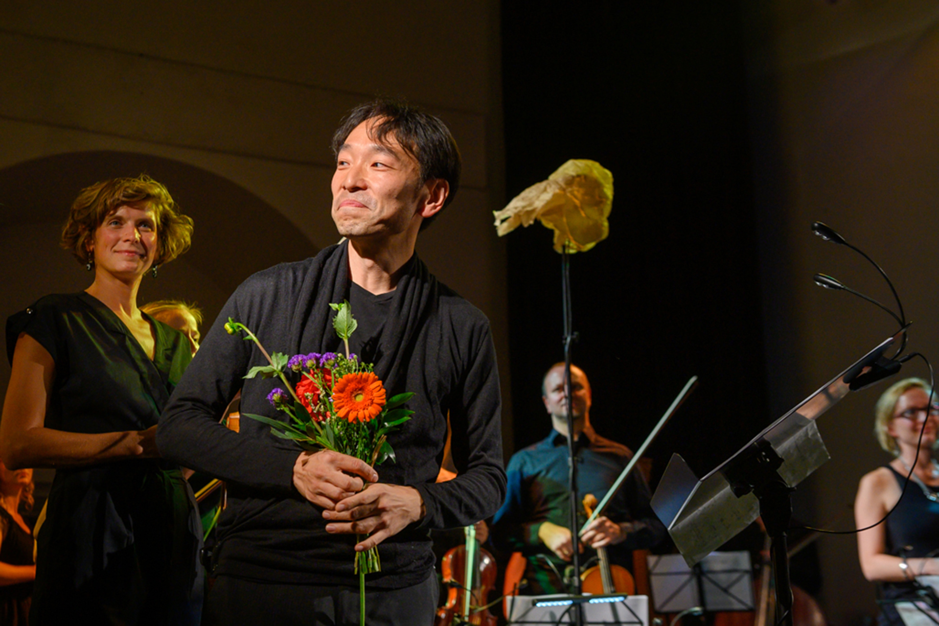 Shown with the Berg Orchestra, Hiroya Miura takes a curtain call after the world premiere of his concerto for shakuhachi in Prague's Domovina Hall in September 2019. (Karel Suster)