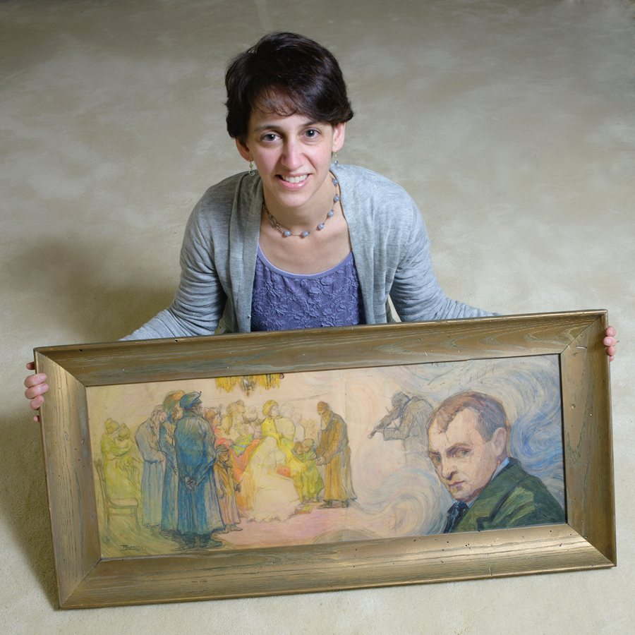 Elizabeth Rynecki '91 poses with a painting by her great-grandfather Moshe Rynecki — a self-portrait that situates the artist beside, but not part of, a wedding ceremony. (Shoey Sindel Photography)