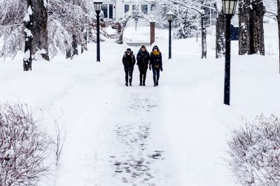 Students navigate a snowy campus this March Monday morning in Maine. From left, seniors Daisy Diamond, Olivia Fried, and Lily Kip navigate the Historic Quad during a March snowfall.