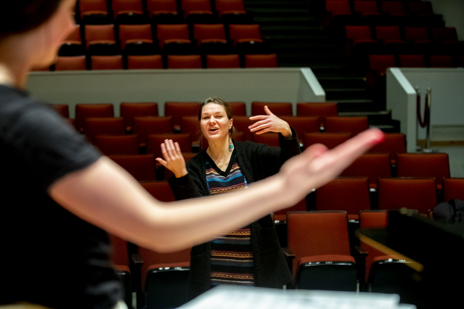 """Joëlle Morris models a gesture for """"The Willow Song"""" by Samuel Coleridge-Taylor as she prepares voice student Clara Porter '22 of Portland, Ore., for an Olin Arts Center voice recital. (Phyllis Graber Jensen/Bates College)"""