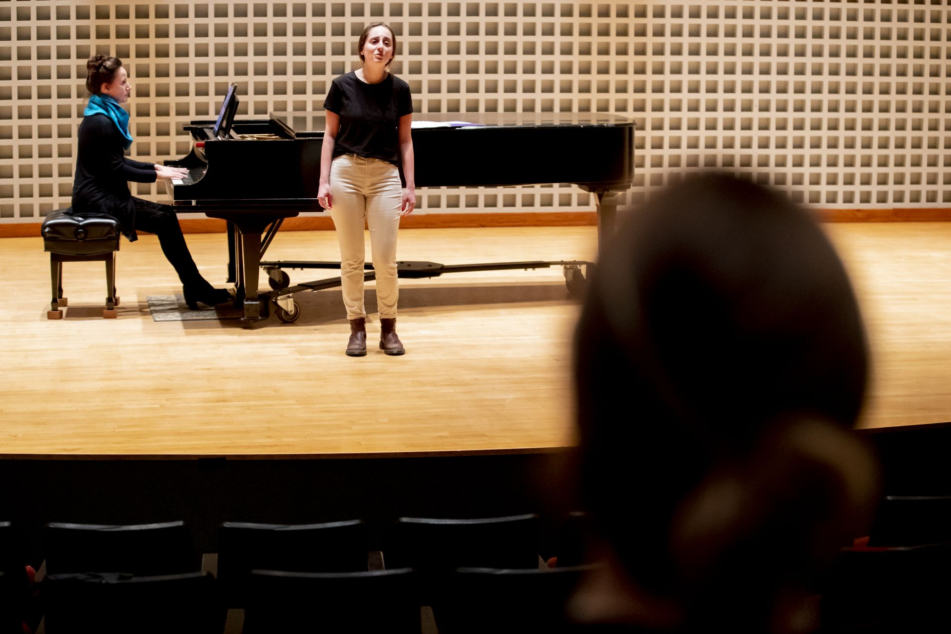 """Accompanied by pianist Bridget Convey, Clara Porter '22 rehearses """"Journey to the Past"""" from """"Anastasia"""" as Joëlle Morris listens in the Olin Arts Center Concert Hall. (Phyllis Graber Jensen/Bates College)"""