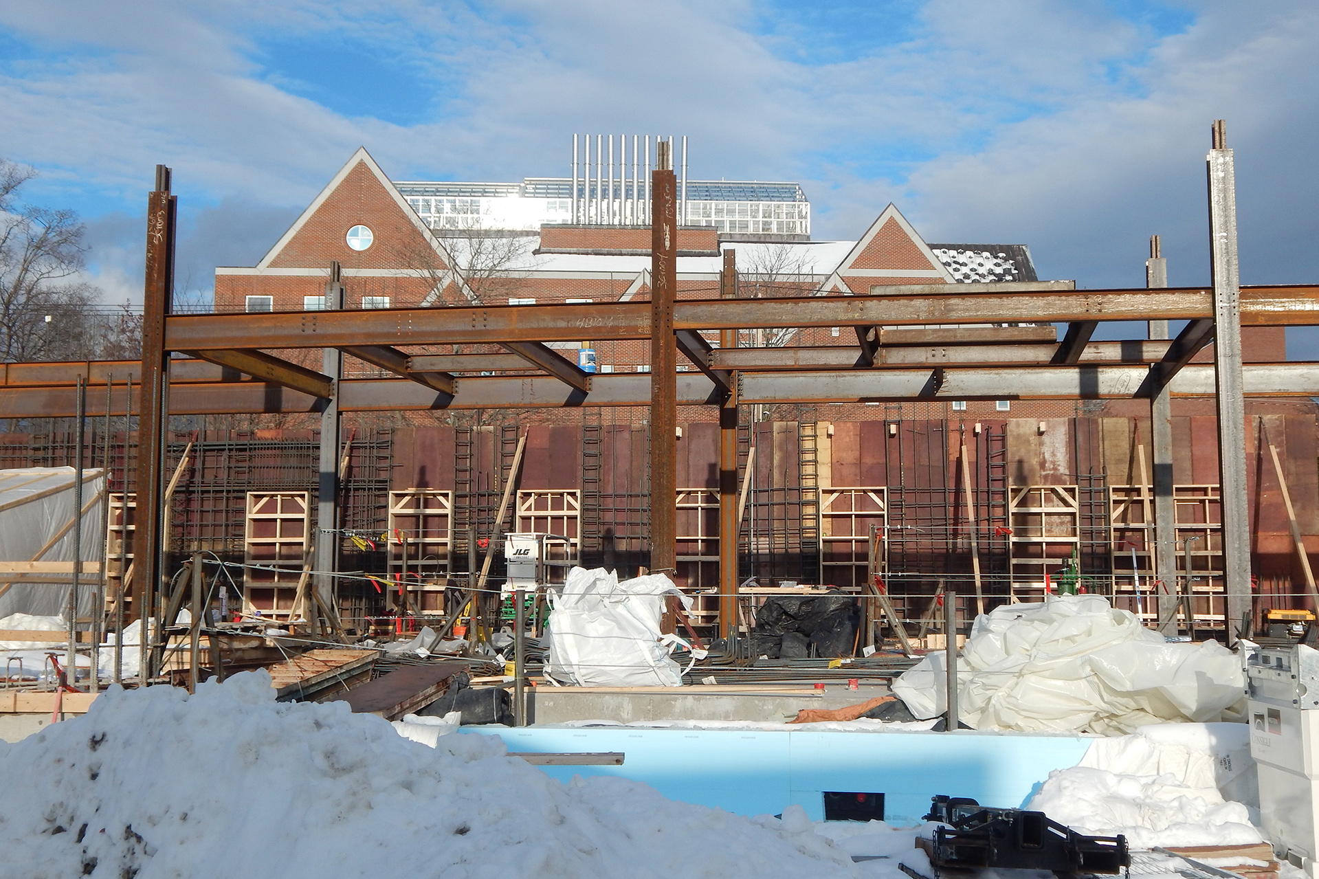 The state of things at the Bonney Science Center in early December 2019. In the background is a wall of concrete forms hung with rebar and window knockouts. Structural steel dominates the image. Showing at the bottom is blue insulation protecting the foundation wall. (Doug Hubley/Bates College)