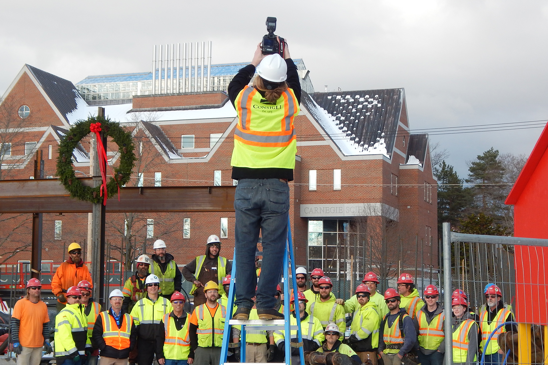 Multimedia producer Theophil Syslo puts the Campus Construction Update ladder to good use on Dec. 5 as he photographs a wreath and workers at the Bonney Science Center. The image was presented to Michael Bonney '80 and Alison Grott Bonney '80, whose family foundation made a gift that is anchoring the building project. (Doug Hubley/Bates College)