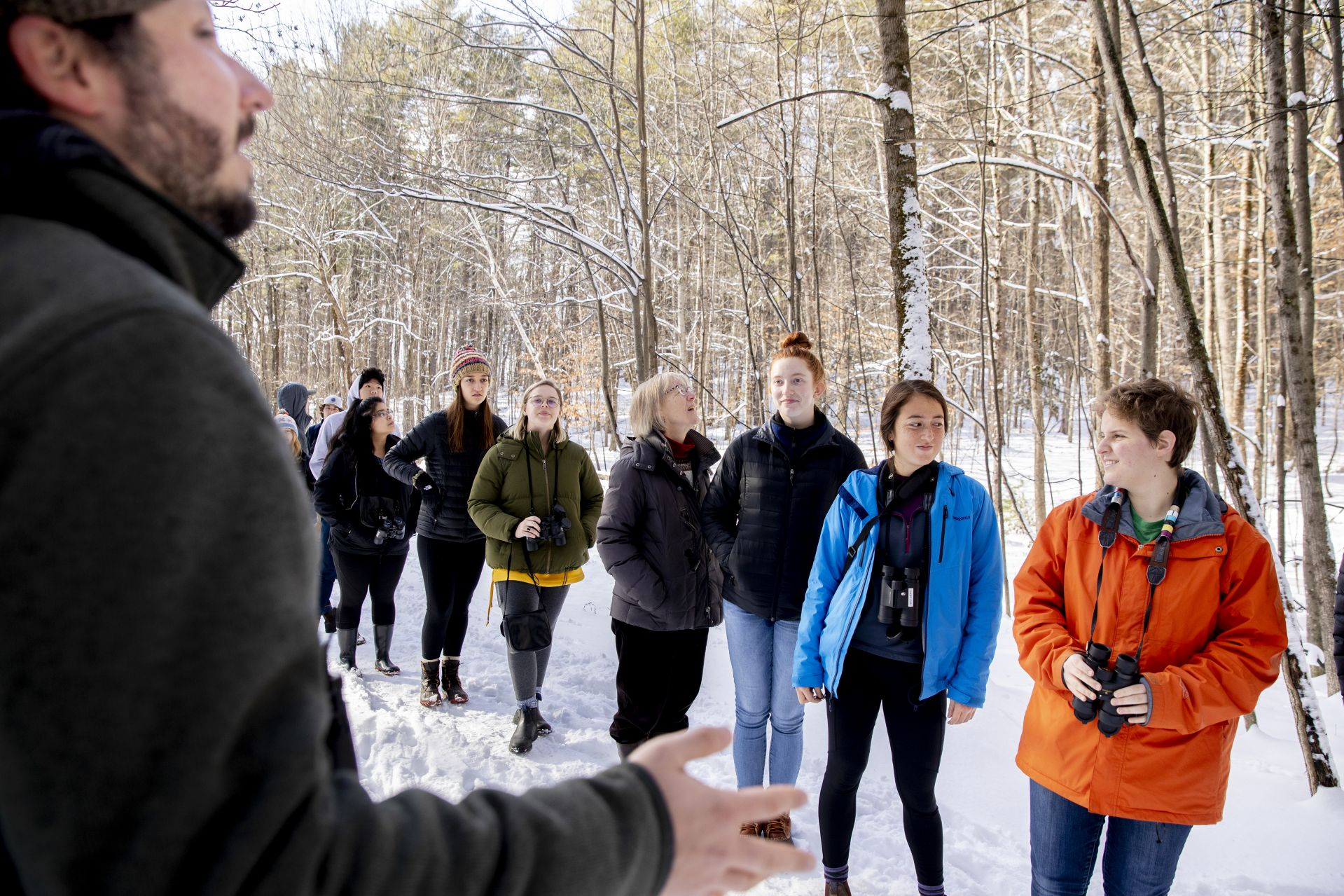 Nick Lund of Maine Audubon demonstrates how birds communicate with each other during a walk in the woods with Costlow and her students in the Thorncrag Bird Sanctuary. (Phyllis Graber Jensen/Bates College)