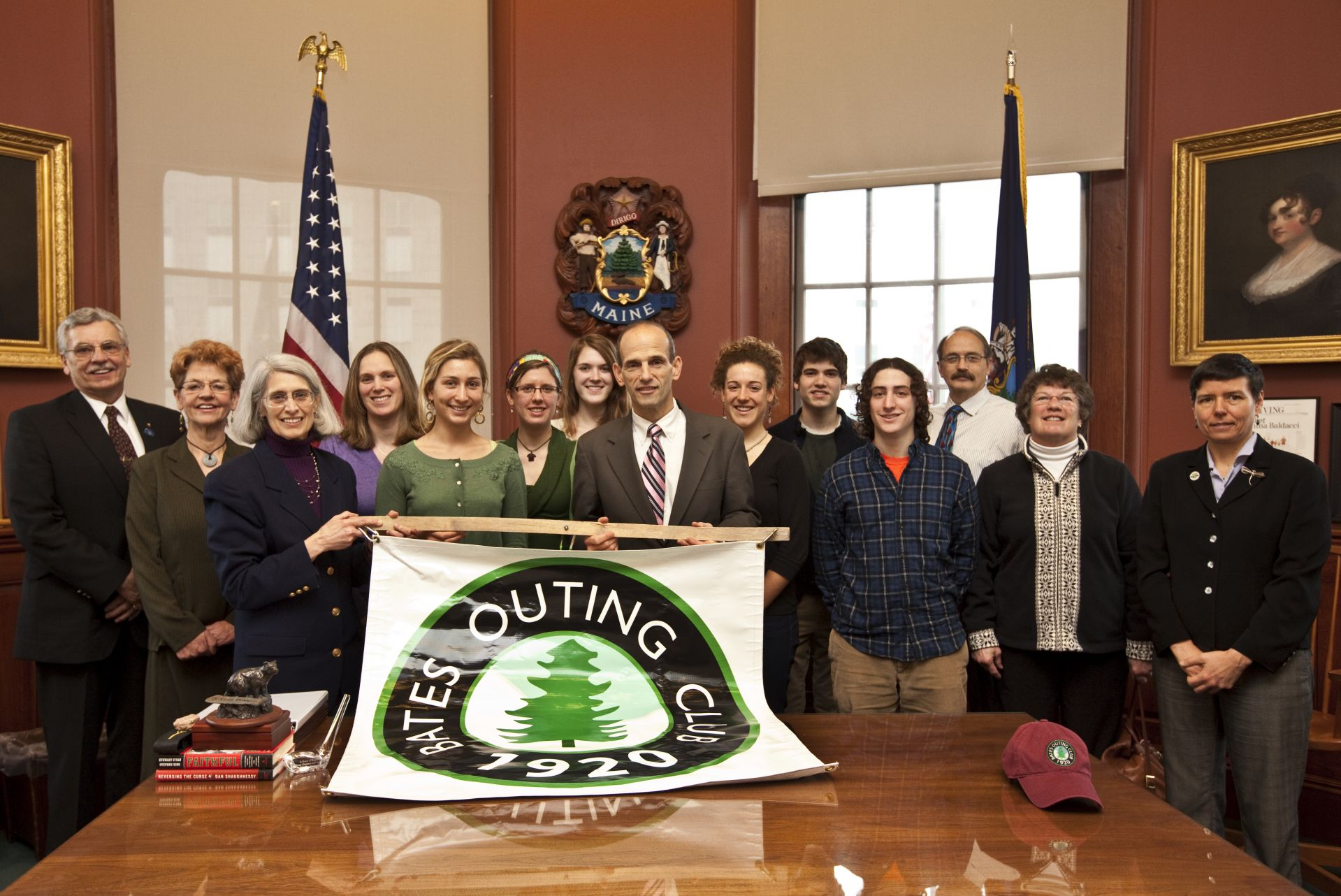 In 2010, Maine Gov. John Baldacci helps the Bates Outing Club celebrate the 90th anniversary of its 1920 founding. From left, Rep. Mike Lajoie (D-Lewiston); Sen. Margaret Craven (D-Lewiston); Rep. Margaret Rotundo (D-Lewiston); Leah Weidmann Gailey '97, Alumni and Parent Programs; Rachel Edwards '11; Ursula Sandstrom '13; Kellen MacFadyen '12, vice president, Bates Outing Club; Gov. Baldacci; JeanMarie Gossard '10, president, Bates Outing Club; Gardiner Nardini '12; Alex Friedman '12; Ken Spalding '73, past president, Bates Outing Club; Judy Marden '66, adviser, Bates Outing Club; Eliza Townsend, acting commissioner, State Department of Conservation. (Phyllis Graber Jensen/Bates College)