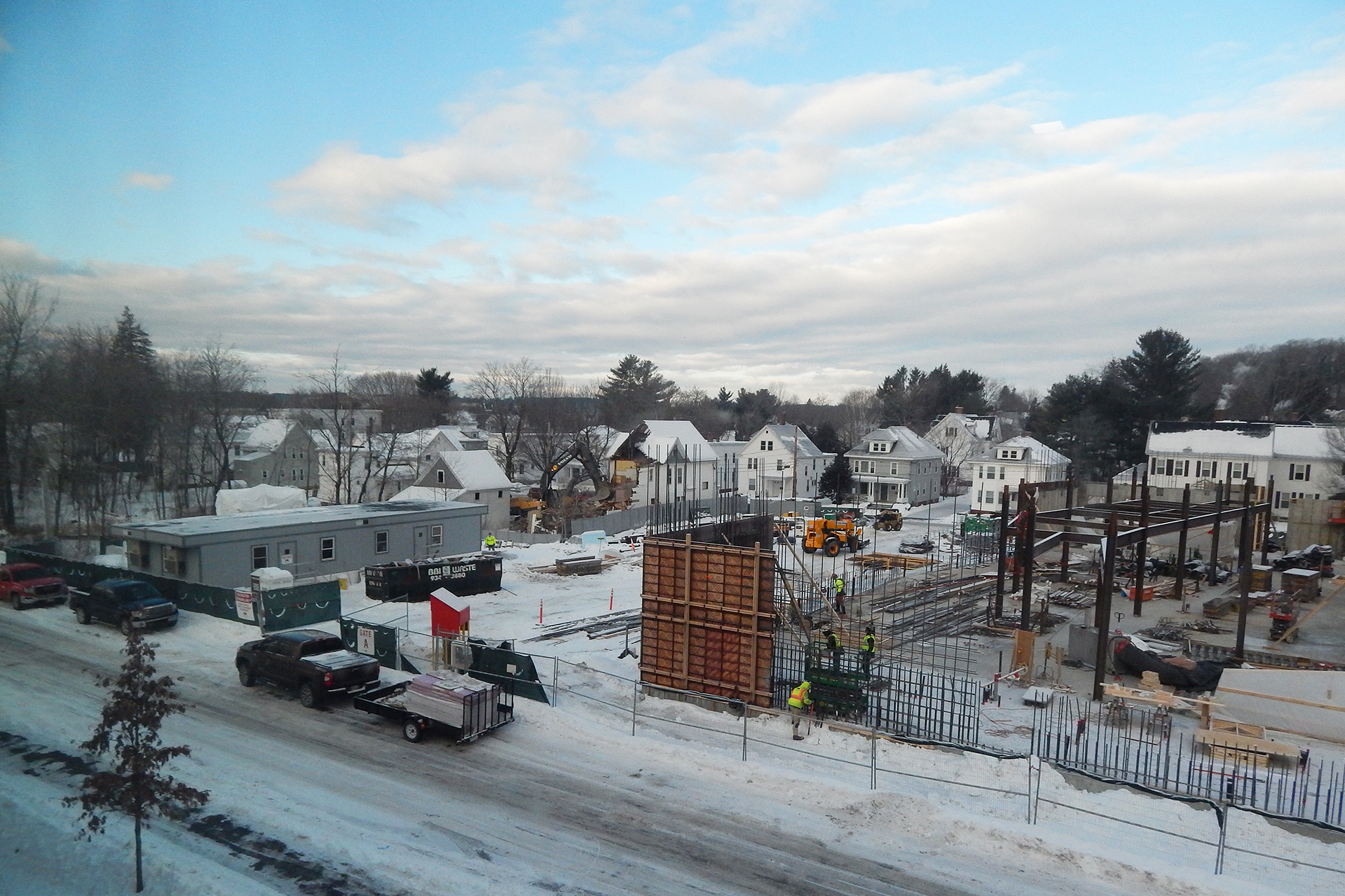 Taken from the third-floor of Chu Hall, facing the Bonney construction site from the east, this Jan. 7 view shows 137 Nichols St. being demolished at center and, nearer the camera, rodbusters assembling rebar for new wall sections at Bonney. (Doug Hubley/Bates College)