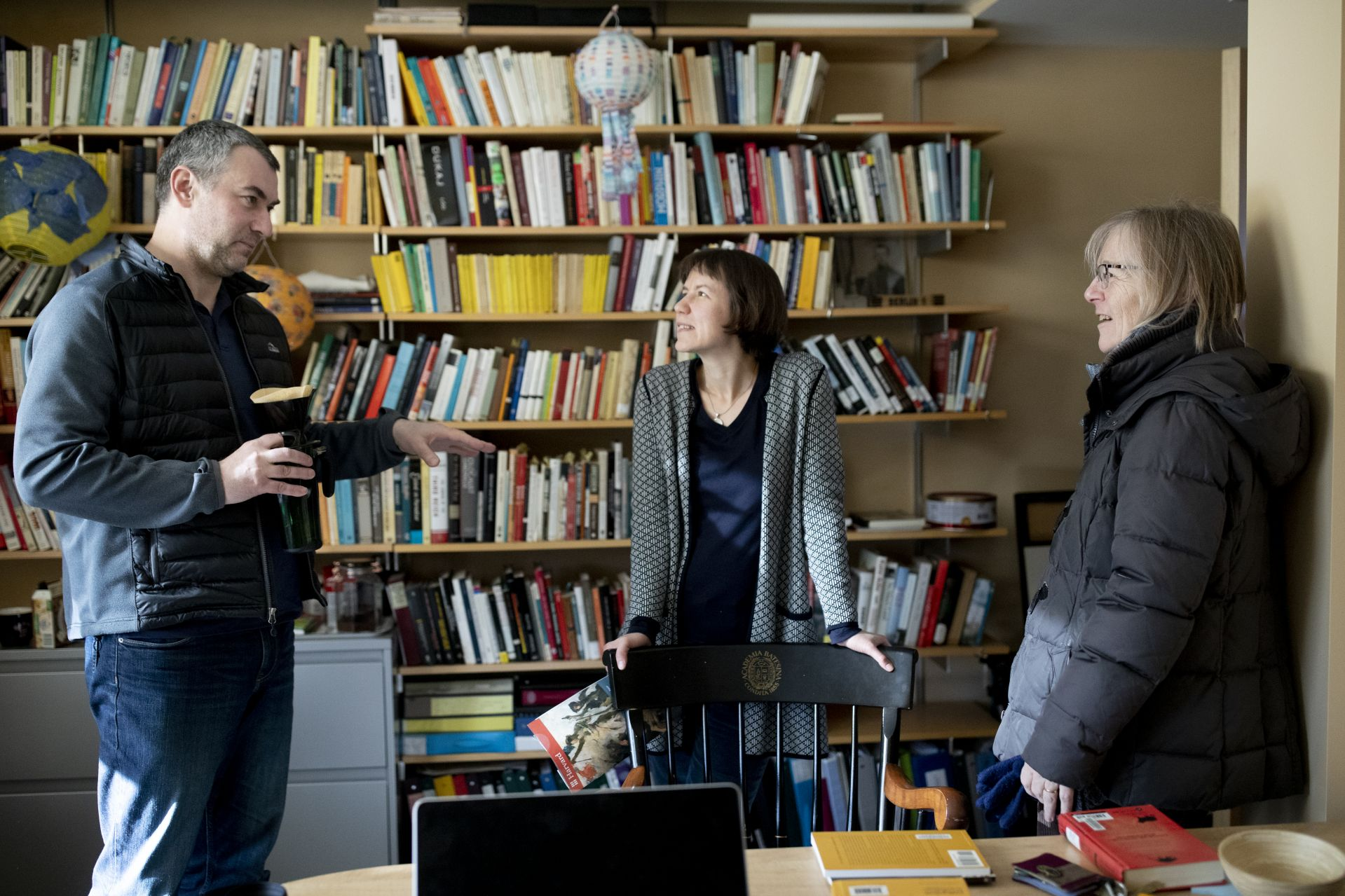 Costlow visits with Associate Professor of German Jakub Kazecki and Associate Professor of German Raluca Czernahoschi in Kazecki's Chase Hall office. (Phyllis Graber Jensen/Bates College)