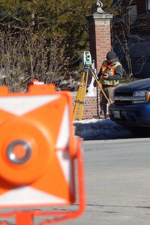 A surveyor at work on Campus Avenue near the Bonney building construction site. (Doug Hubley/Bates College)