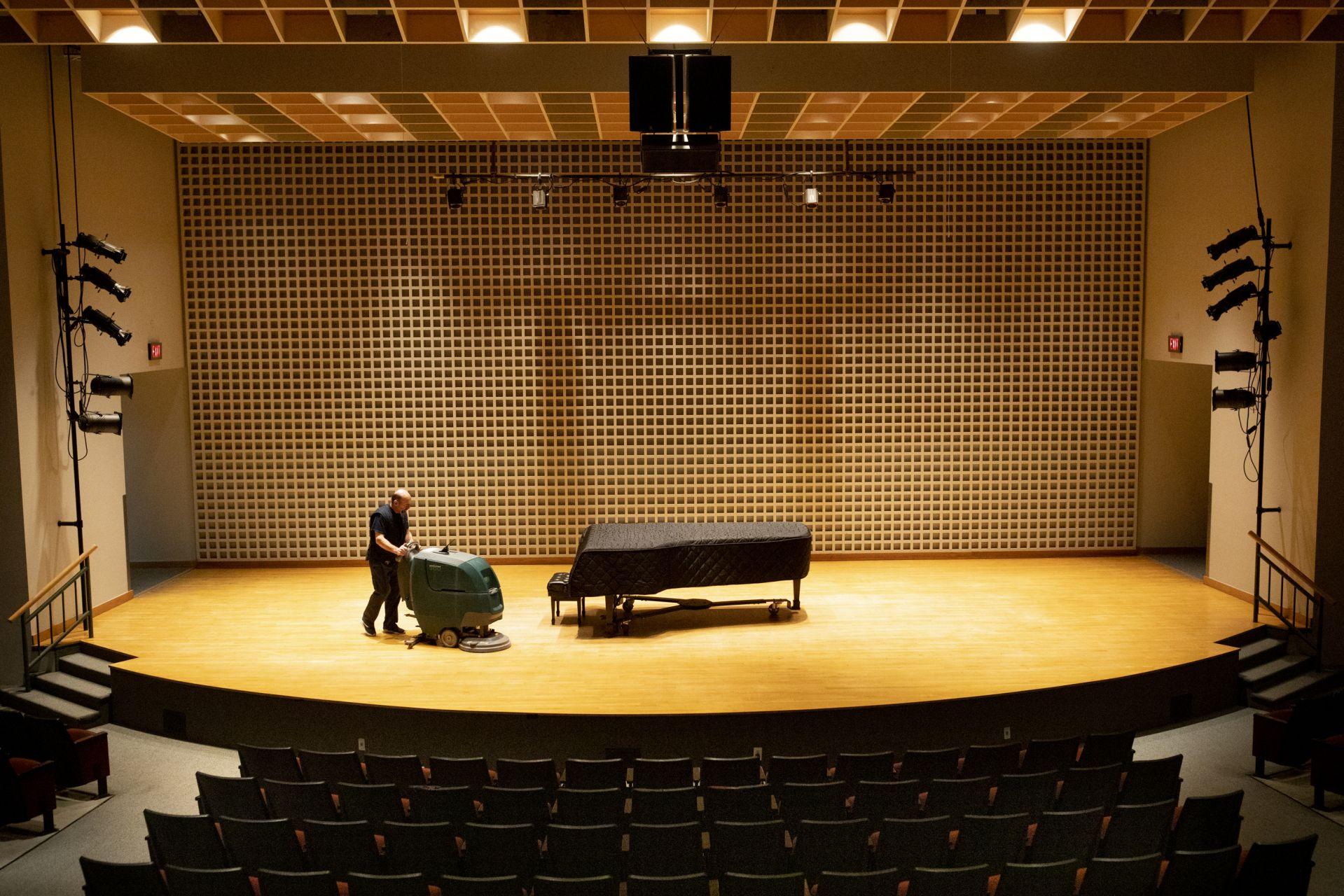 Olin Arts Center Custodian Bruce Audet cleans concert stage floor.