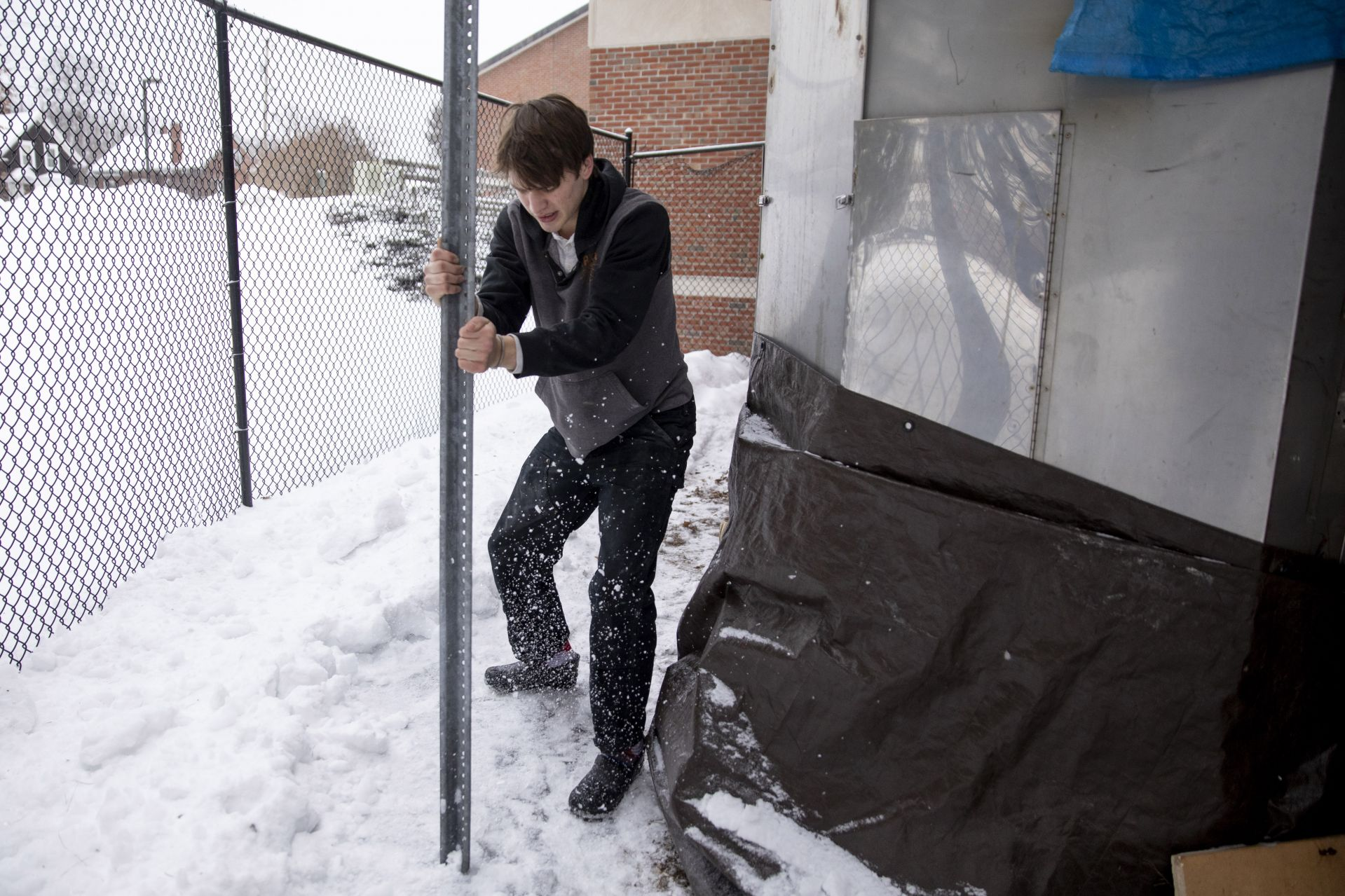 Olin Arts CenterAlex Paton '21, a double major goes the extra mile to break up the snow and ice behind the outdoor soda kiln so the burners will fit on its back. This kiln creates a special glaze.