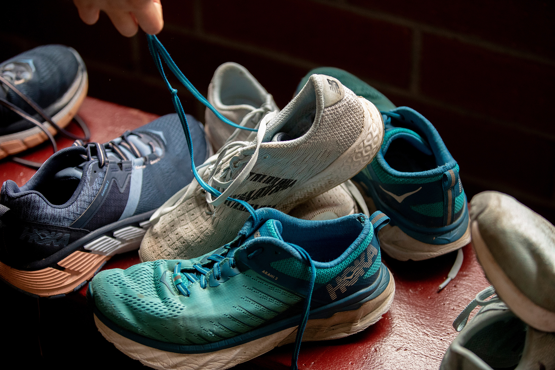 """Caroline """"Carly"""" Harris '22 of Orinda, Calif.,with worn-out shoes, examples of what she will be recycling in the lobby of Merrill Gymnasium."""