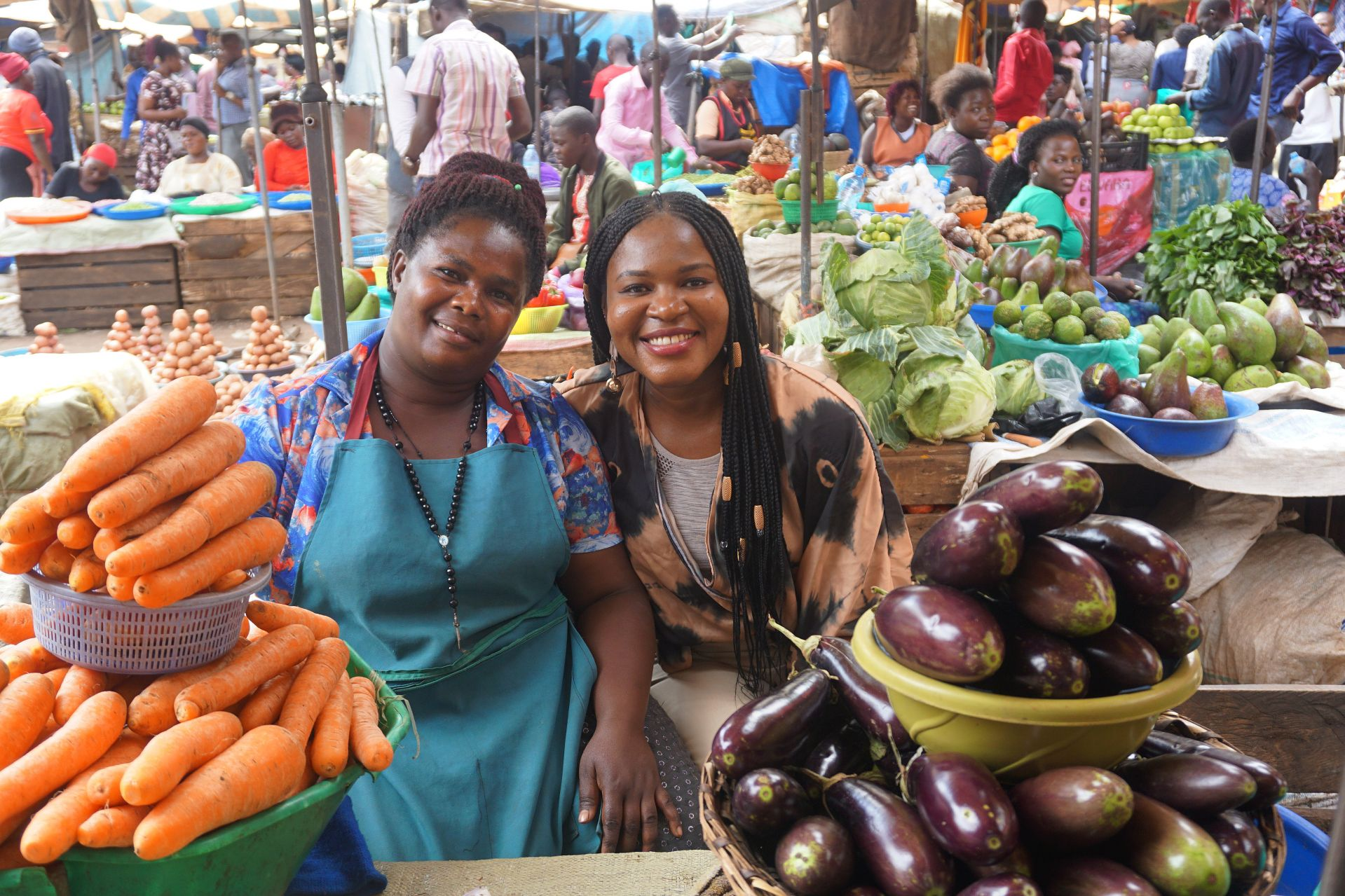 Linda Kugblenu '13 (right), who has a Fulbright Student research award in Uganda, poses with Dorothy, an entrepreneur who sells and fruits and vegetables in the Nakasero Market in Kampala. Kugblenu is leading focus groups with female entrepreneurs to explore savings and credit cooperatives, or SACCOs, which are significant drivers in the mobilization of women to acquire capital, invest in businesses, and become financially stable.