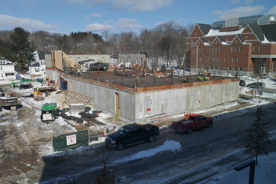 "The Bonney Science Center seen from the east on Feb. 20, 2020. ""Rod busters"" are wiring down rebar for the second-story floor slab at the right, and at rear, wall sections have been placed at the west end. (Doug Hubley/Bates College)"
