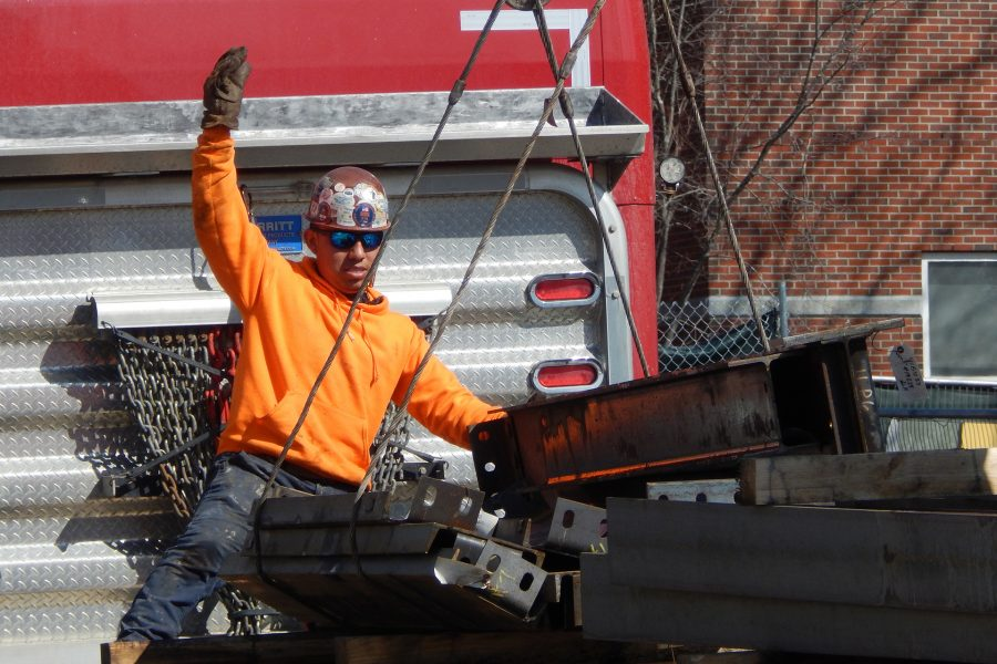 A steelworker gives the signal for the crane operator to hoist a load of components for the Bonney center skeleton on March 3. (Doug Hubley/Bates College)