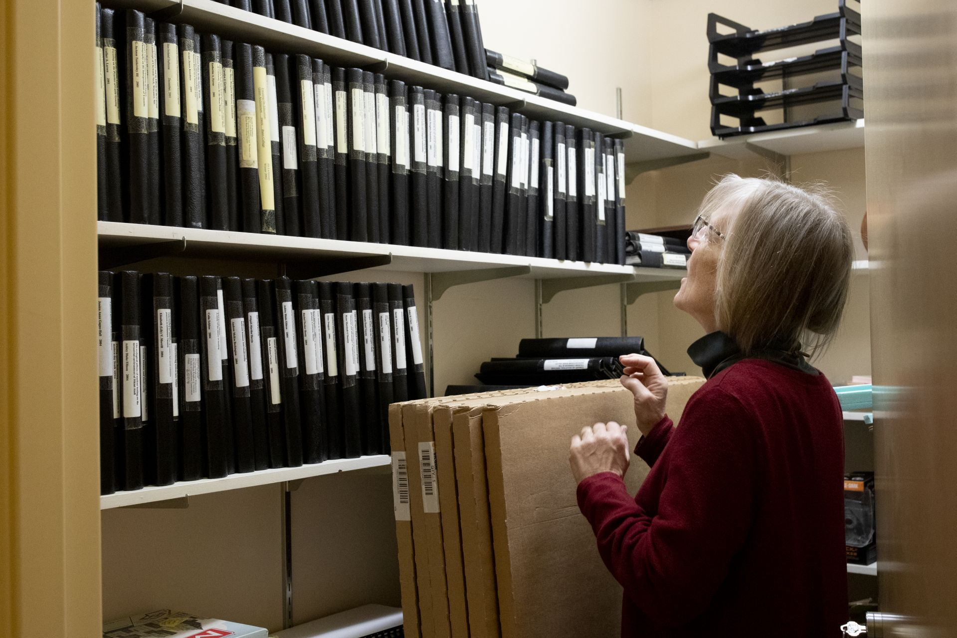 Costlow inspects thesis binders stored in the environmental studies department. (Phyllis Graber Jensen/Bates College)