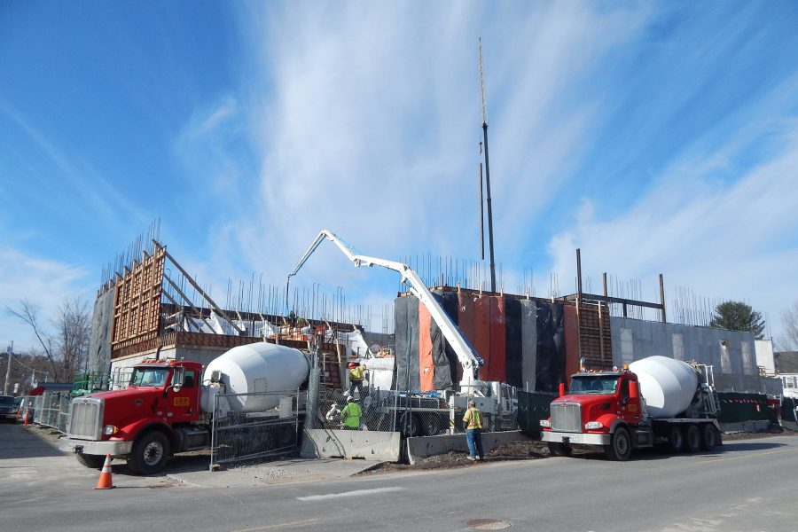 With the next load already lined up, the pumper at center sends concrete through the boom clear across the Bonney center footprint to build a wall on the far side. Meanwhile, new steel dangles over the building from a crane. (Doug Hubley/Bates College)