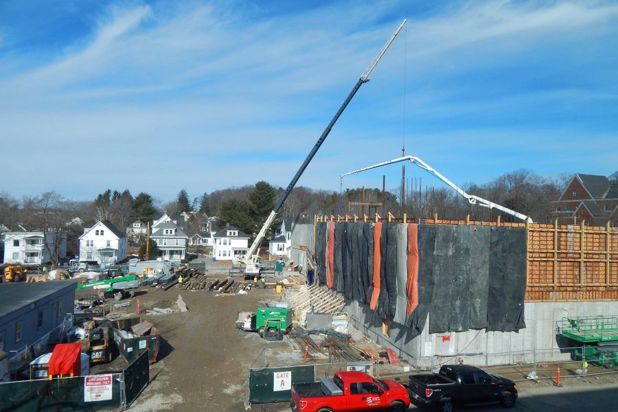 A telescoping-boom crane, left of center, hoists steel onto the second floor of the Bonney center while the boom of a concrete pump hovers over a new wall placement on the south side. (Doug Hubley/Bates College)