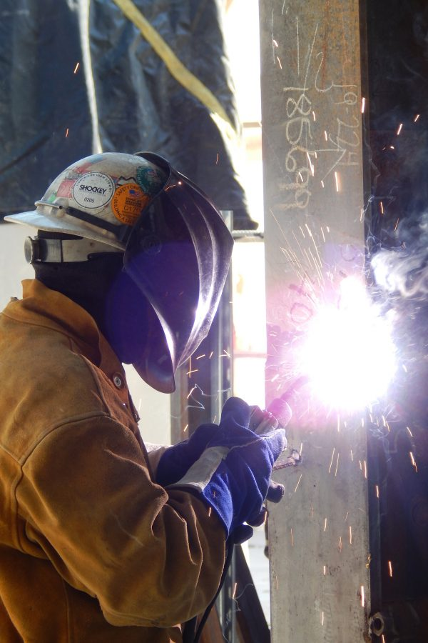 A welder for Precision Steel works on a seam on the Bonney center's second floor. (Doug Hubley/Bates College)