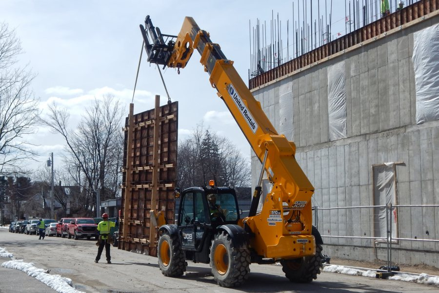A Lull-style forklift totes a section of Symons wall form down Bardwell Street toward the Bonney Science Center service area. (Doug Hubley/Bates College)