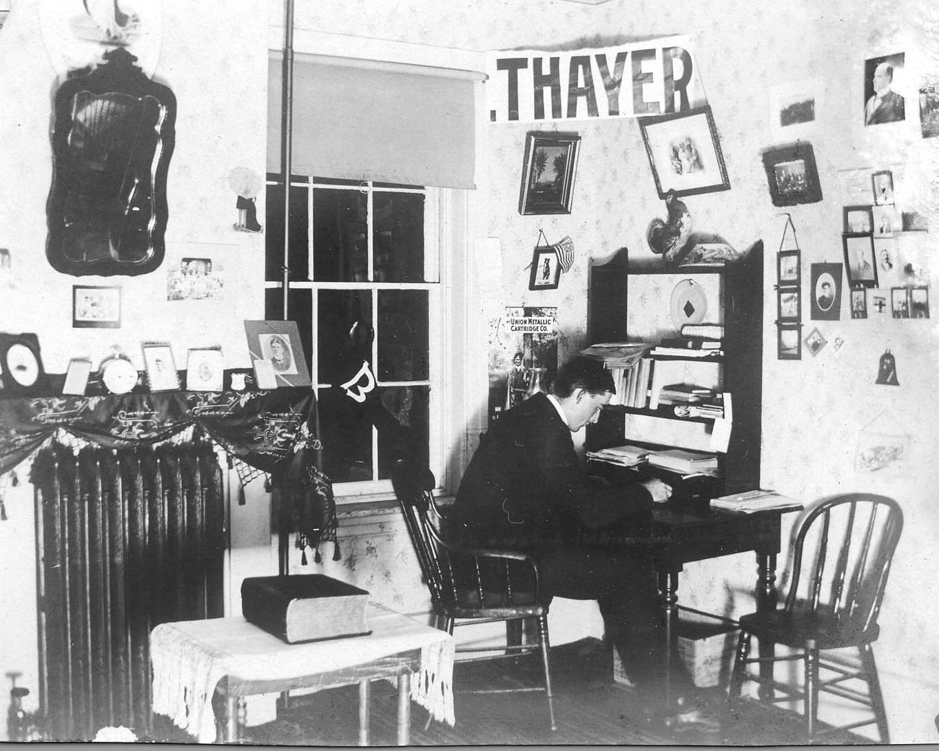 In 1903, Harold H. Thayer, Class of 1903, studies in his Parker Hall room. (Muskie Archives and Special Collections Library)