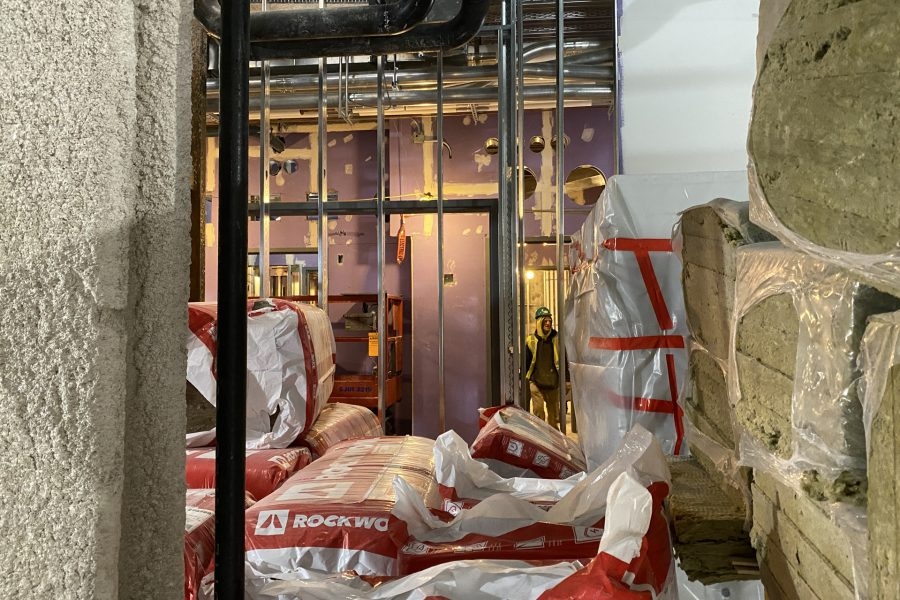 A worker passes insulation stockpiled in the Bonney center basement. (Geoff Swift/Bates College)
