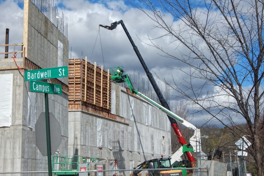 As soon as the white and green manlift makes way, the telescoping-boom crane will peel a section of Symons concrete form off the new third-story wall. (Doug Hubley/Bates    College)