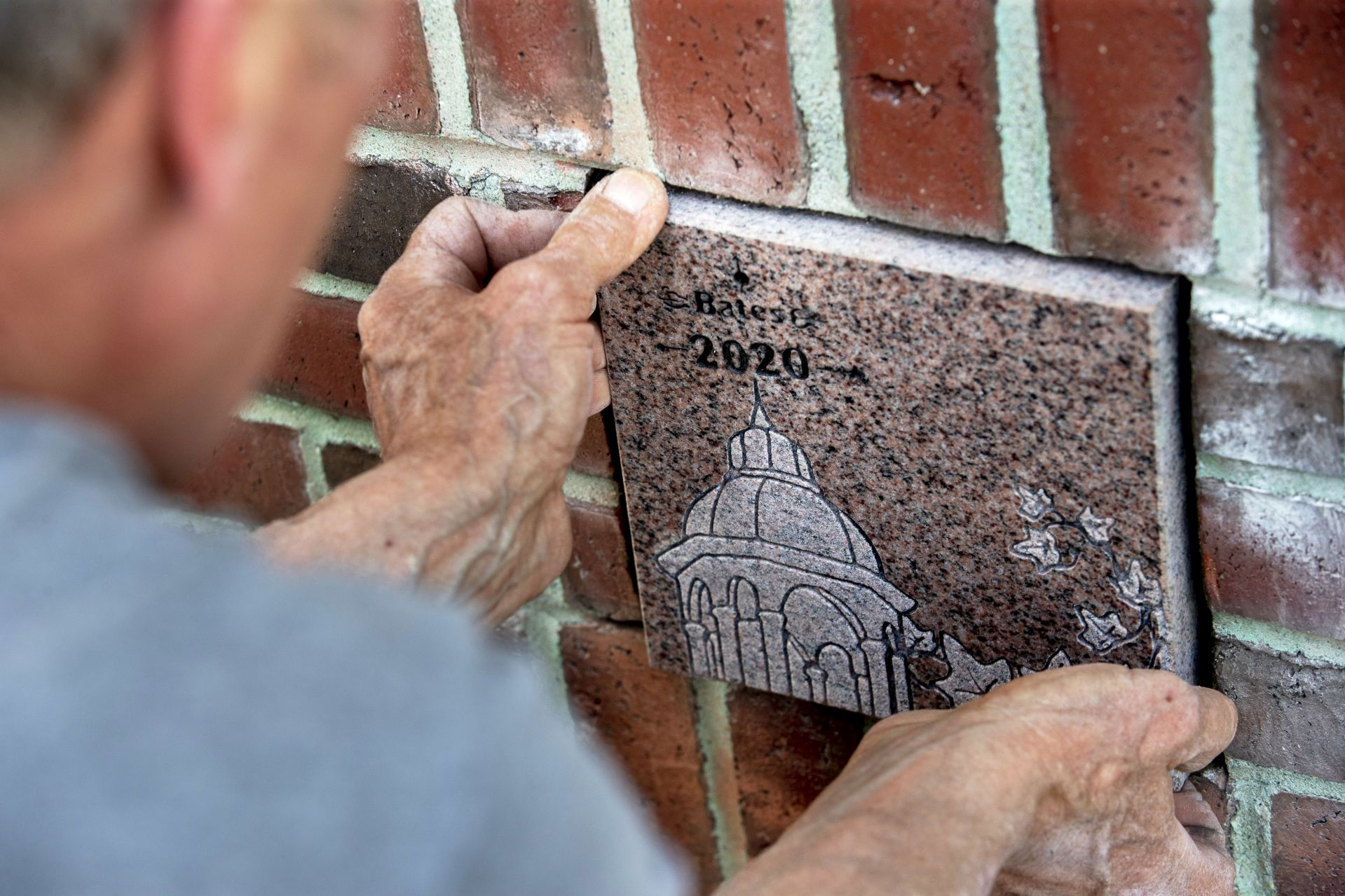 Ron Tardif, mason for facility services, installs the Class of 2020 ivy stone on the front of Pettentill Hall, to the right of the building's entrance.