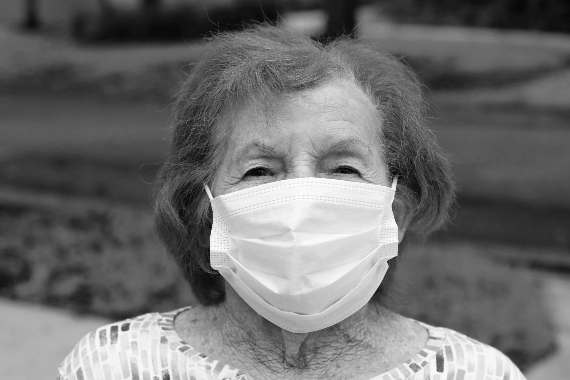 Wearing her mask, Pauline Petrin, age 92, sits outside after a walk around her neighborhood in Plantation, Fla., on April 17, 2020.