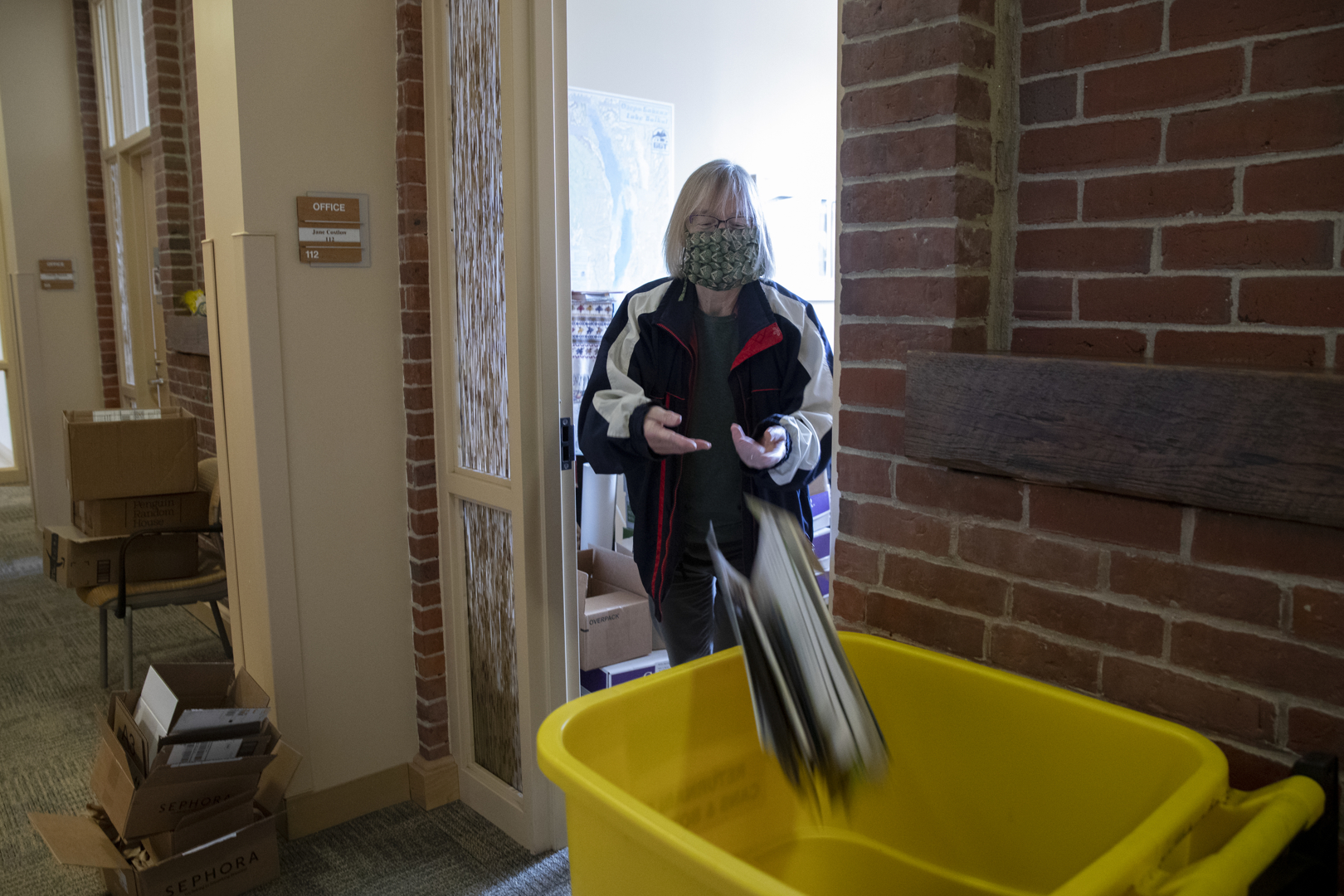 Costlow tosses some papers into a recycling bin outside of her Hedge Hall office. (Phyllis Graber Jensen/Bates College)