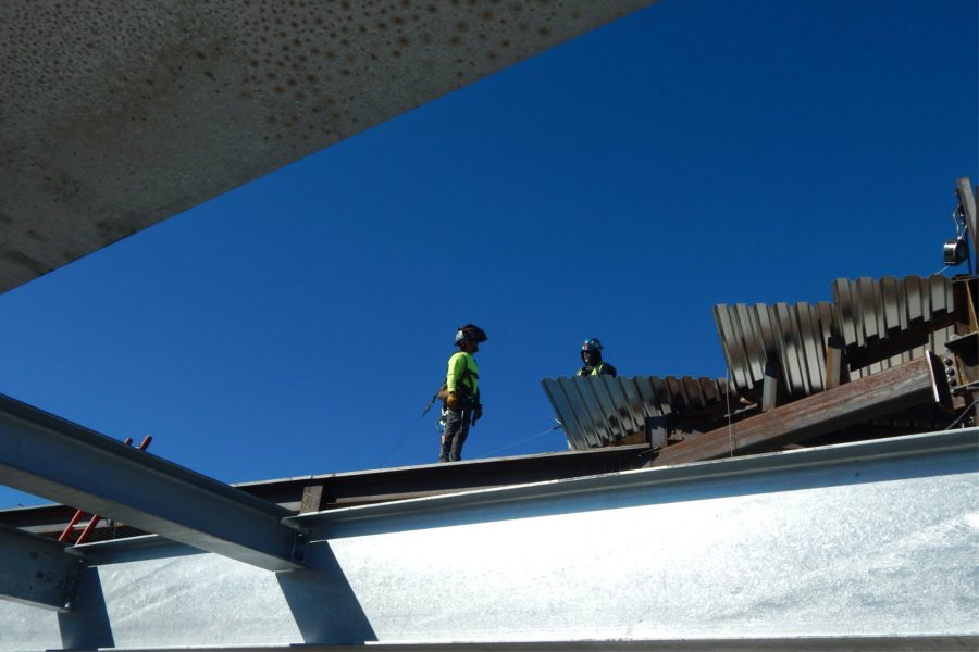 Steelworkers confer atop the roof decking. (Doug Hubley/Bates College)