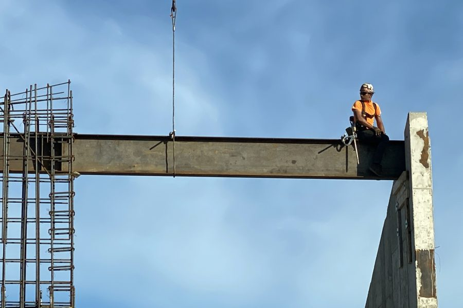 On June 123, a steelworker perched on a just-placed beam looks to a co-worker for a signal. (Geoff Swift/Bates College)