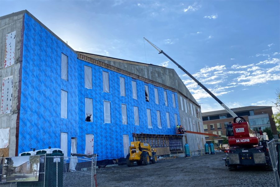 "Gray turns to blue: ""Blueskin"" weatherproofing application has begun. Bricks will follow. Note the opening for the building entrance at center: The wall above it functions as a so-called vierendeel truss. (Geoff Swift/Bates College)"