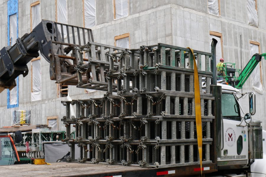Shown being unloaded by a forklift, components for the Hydro Mobile staging — so-called mast-climbing work platforms that are hydraulically raised and lowered — showed up on July 13. They were delivered by Maine Masonry, which will use them for bricklaying. (Doug Hubley/Bates College)