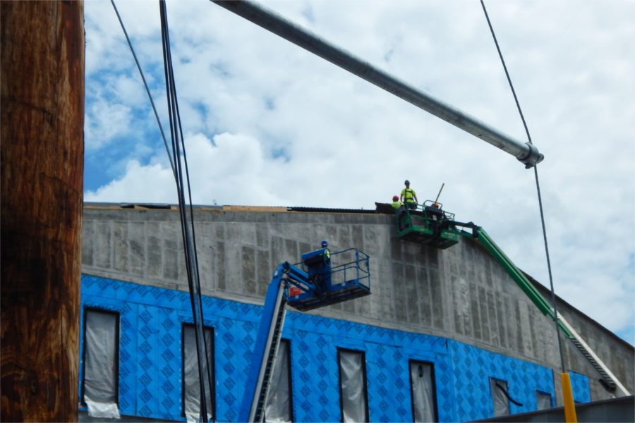 Roofers applying a temporary weather barrier on the south side of the science center. (Doug Hubley/Bates College)