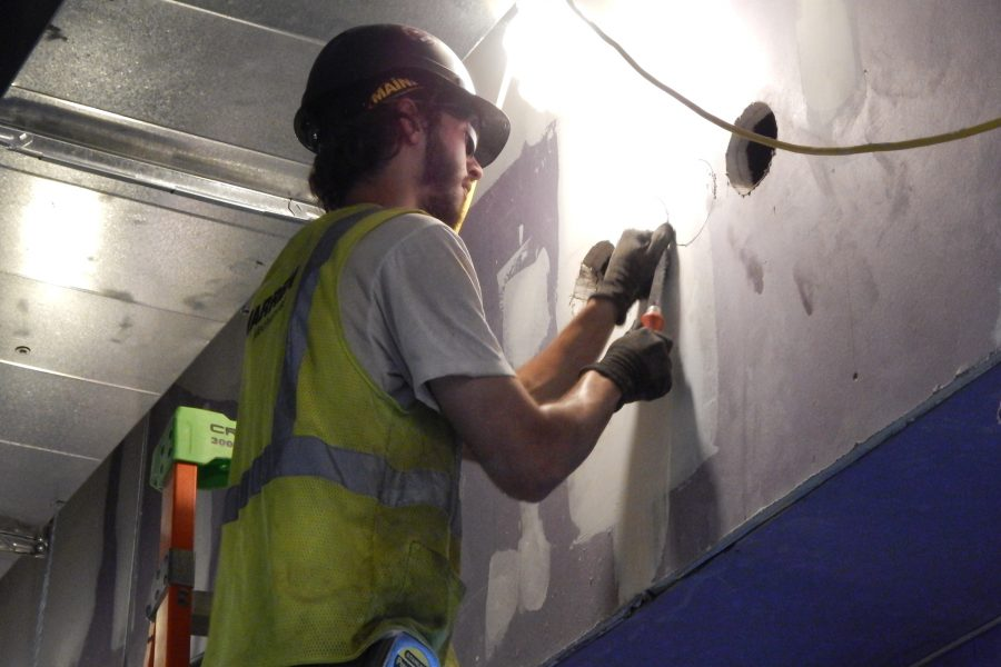Preparing to cut a hole for a conduit on the first floor of the science center. (Doug Hubley/Bates College)
