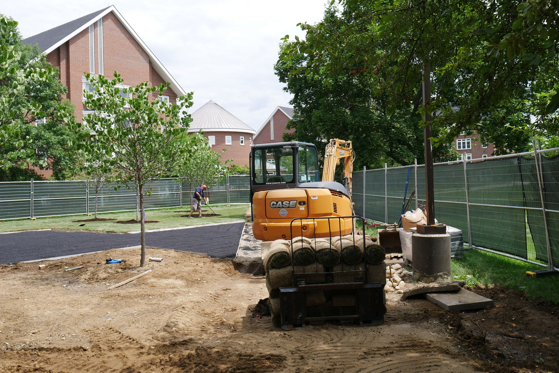 At work on the Veterans Plaza project on July 13. In the background is the Residential Village, and in the foreground is a load of sod rolls. (Doug Hubley/Bates College)