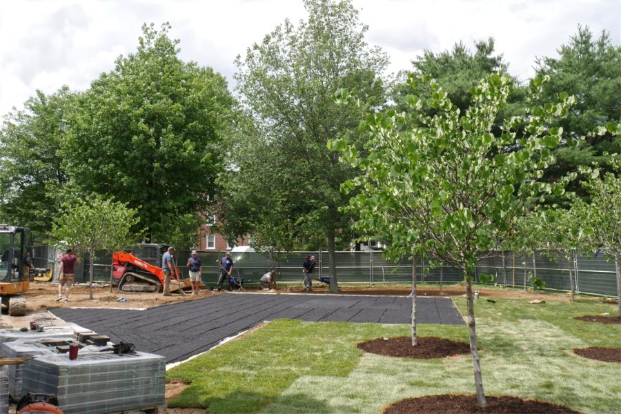 A crew from Carrier Lawn Care & Landscaping of Lewiston lays sod at the Veterans Plaza site. On pallets at left are asphalt pavers for the project. (Doug Hubley/Bates College)