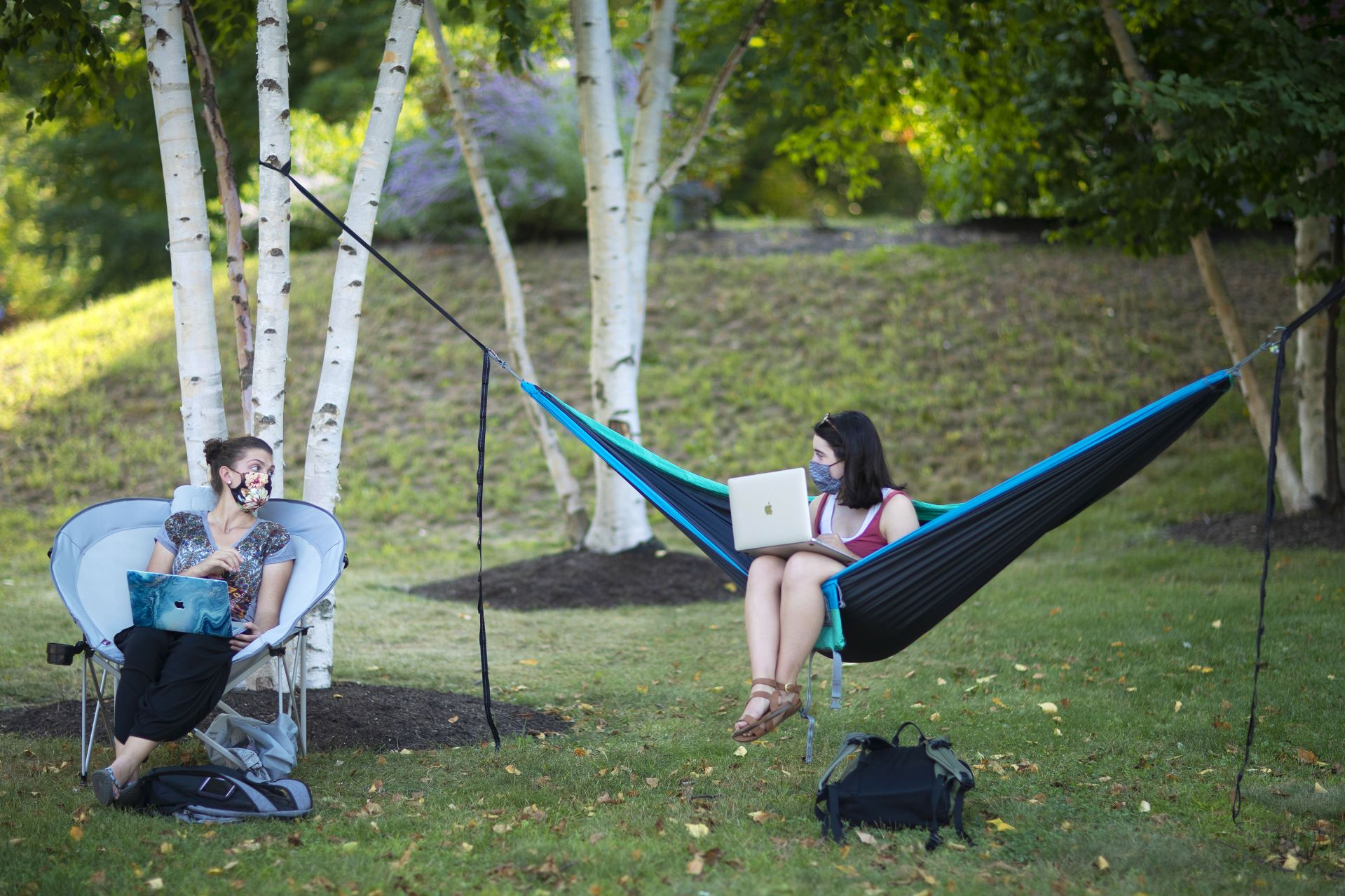 Campus scenes on Sept. 8, 2020.  From left, roomates Svea Althausen '24 of Reno, Nevada, and Katherine Buetens '24 of Orono, Maine, enjoy studying outside along Alumni Walk in front of Hathorn Hall.  Althausen likes the camp chair because she can pop it open across campus as she likes – and it's really comfy, she says. She finds it difficult to study in a hammock because the swaying interferes with her concentration. She was studying for INDS 295 - Afro-diasporic Activism   Buetens received the hammock as a high school graduation gift from her mother. FYS Vaccines taught by Bruno Salazar-Perea