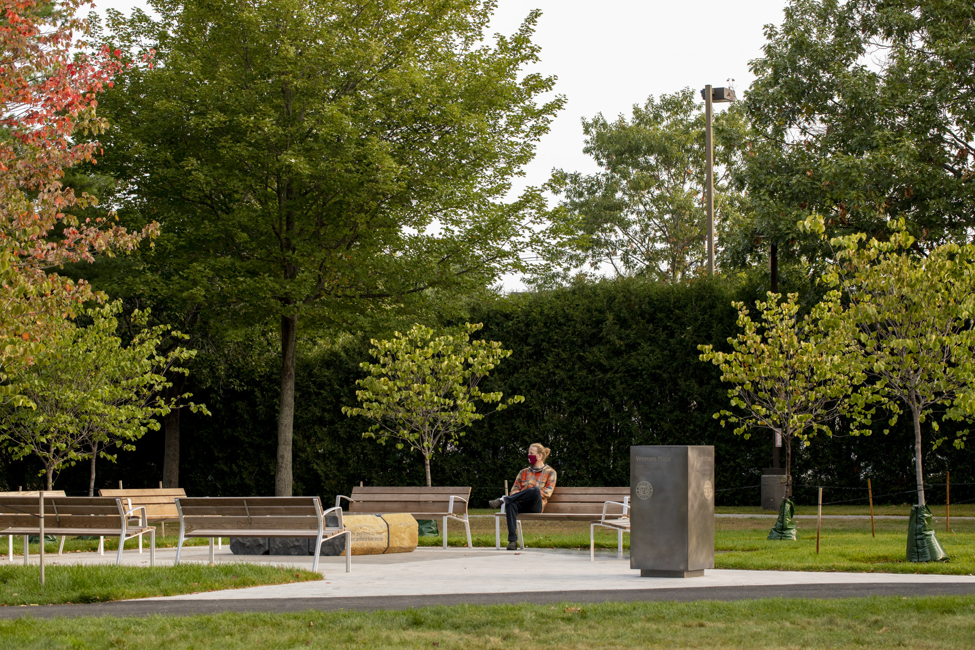 Enjoying Veterans Plaza in the early morning. The marker designating the site is in the foreground and the low stone piece between two benches is a basalt sculpture designed to promote focus and contemplation. (Phyllis Graber Jensen/Bates College)