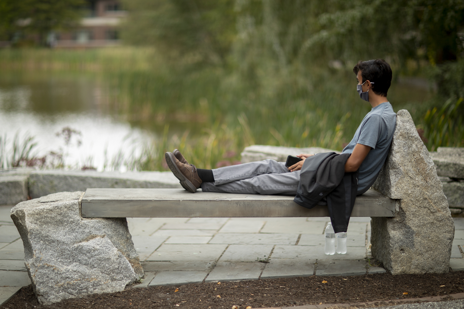 Cameron Frary '24 of Andover, Mass., gazes out over Lake Andrews after  finishing his lunch. This bench is one of his two favorite places, the other also adjacent to the Puddle. Frary is a new member of the Bates sailing club, so he's drawn to a water environment.