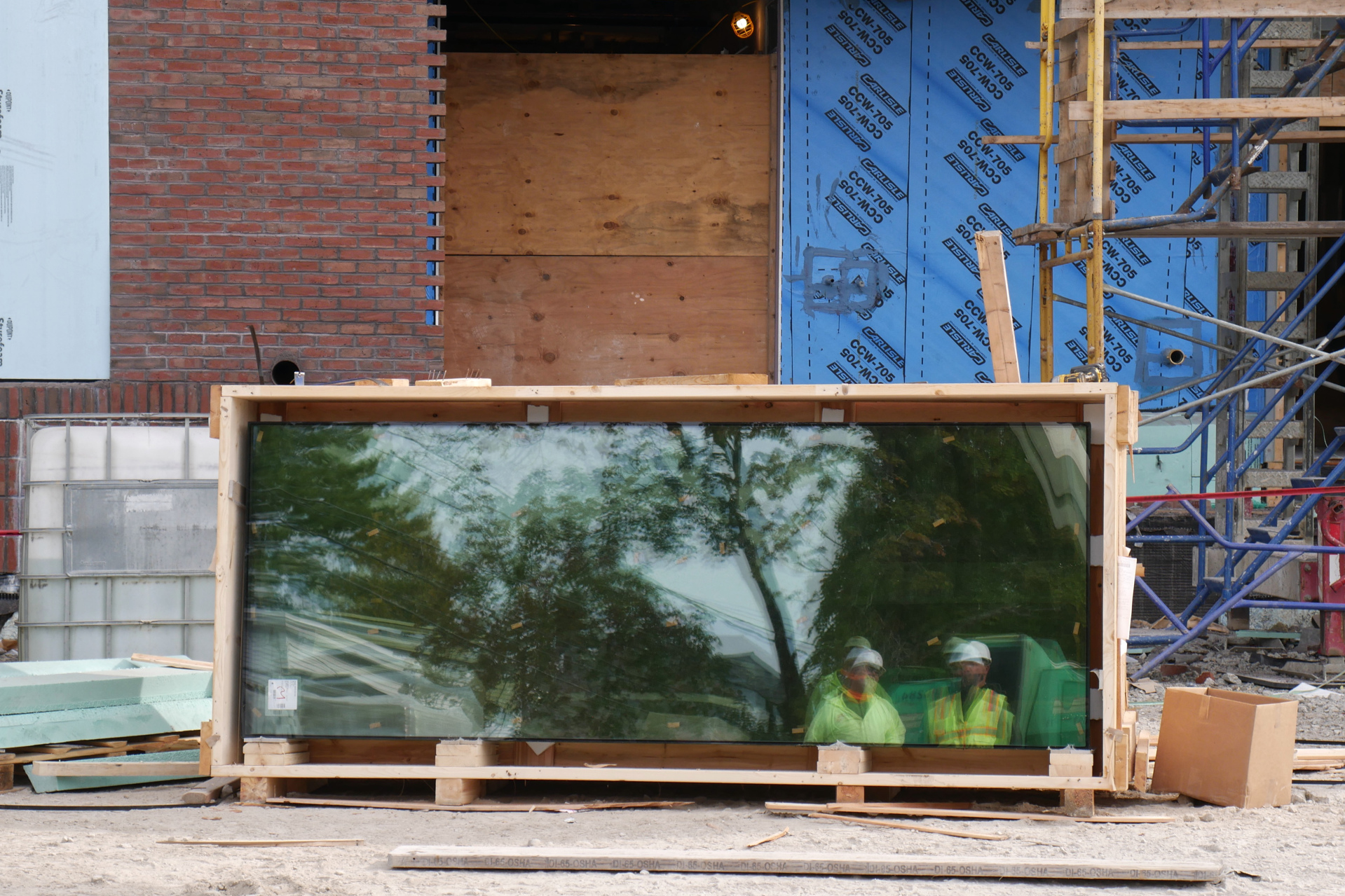 Members of the construction team are reflected in new window glass stored behind the science center. (Doug Hubley/Bates College)
