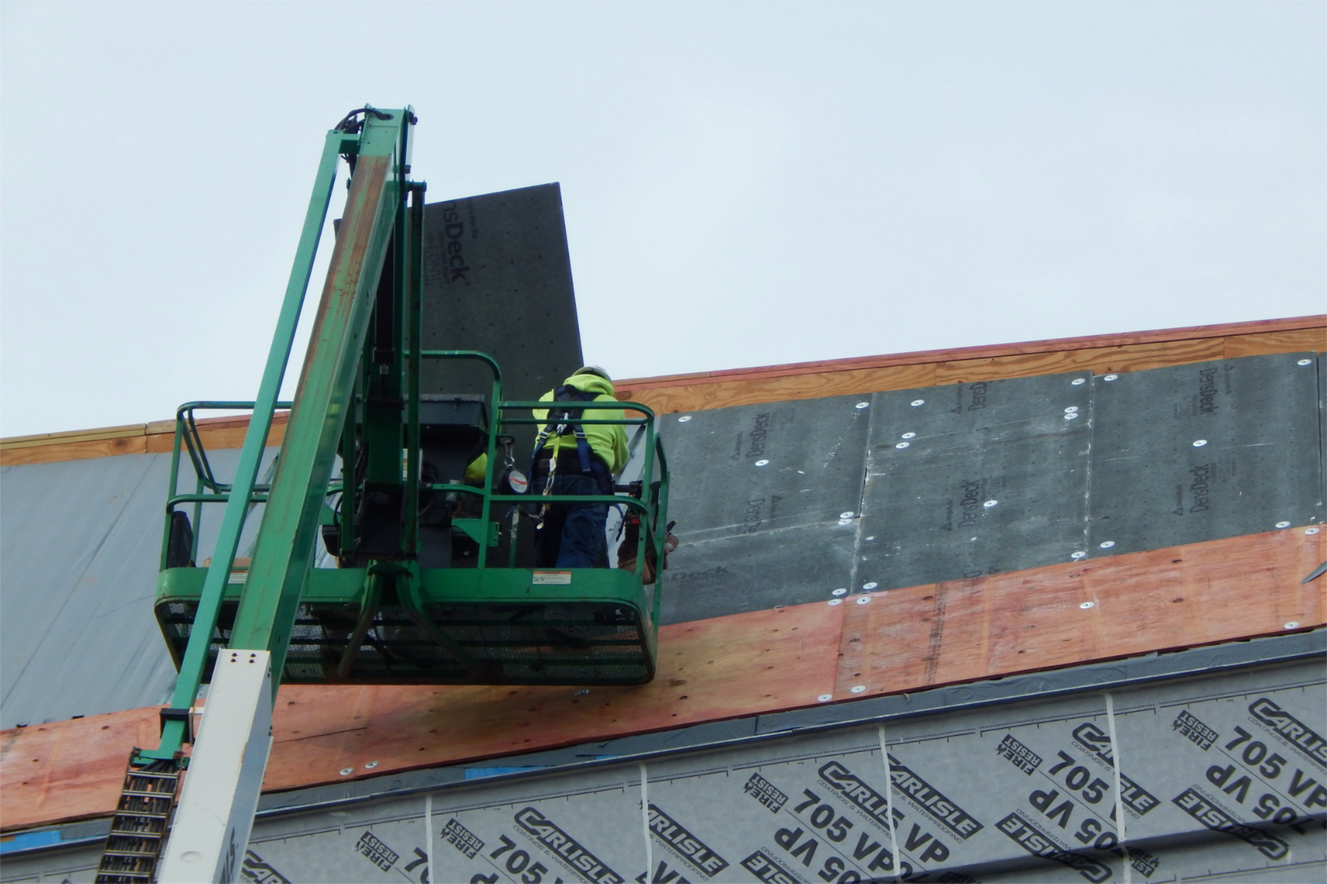Placing a DensDeck roof panel over temporary weatherproofing (at left) on Sept. 22. (Doug Hubley/Bates College)