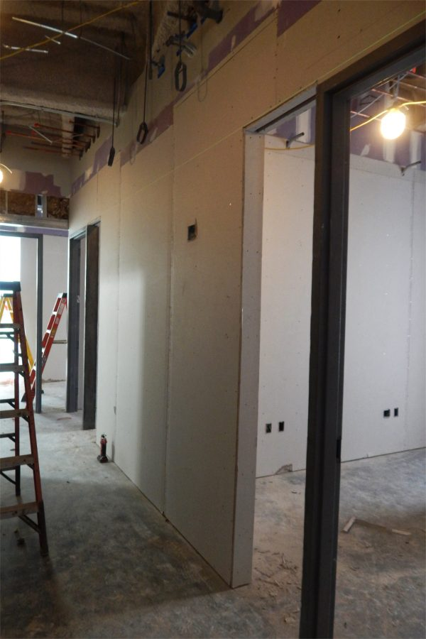 Paint and drywall are forming rooms and hallways from empty space. The opening to the left of the doorframe will hold a glass insert. (Doug Hubley/Bates College)