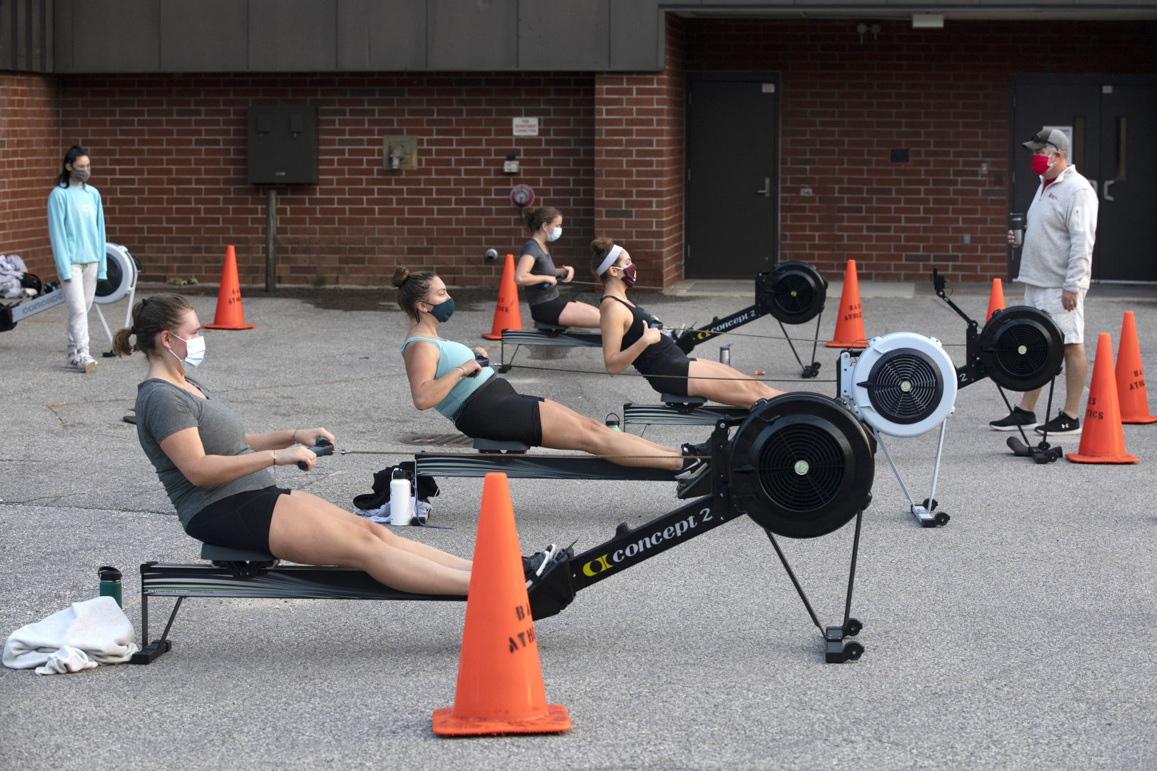 Women's rowing practice with Peter Steenstra and the erg machines behind Merrill Gym on Sept. 17, 2020.  Athlete in black with headband: Eliza Fischer '21 of Chicago,  Athlete with gray t-shirt and pony tail:  and Eloise Botka '23 of Cambridge, Mass.