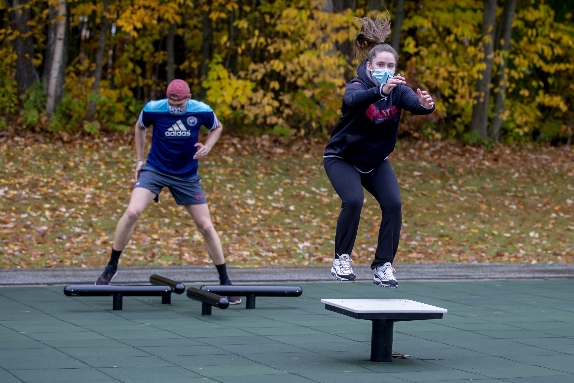 The joint is jumping: During Oct. 21 workouts at Bates' new fitness park, Freddy Hohmann '22 of Bonn, Germany, uses the log hop while Julia Middlebrook '21 of Ridgefield, Conn., springs onto a plyometric step. (Phyllis Graber Jensen/Bates College)