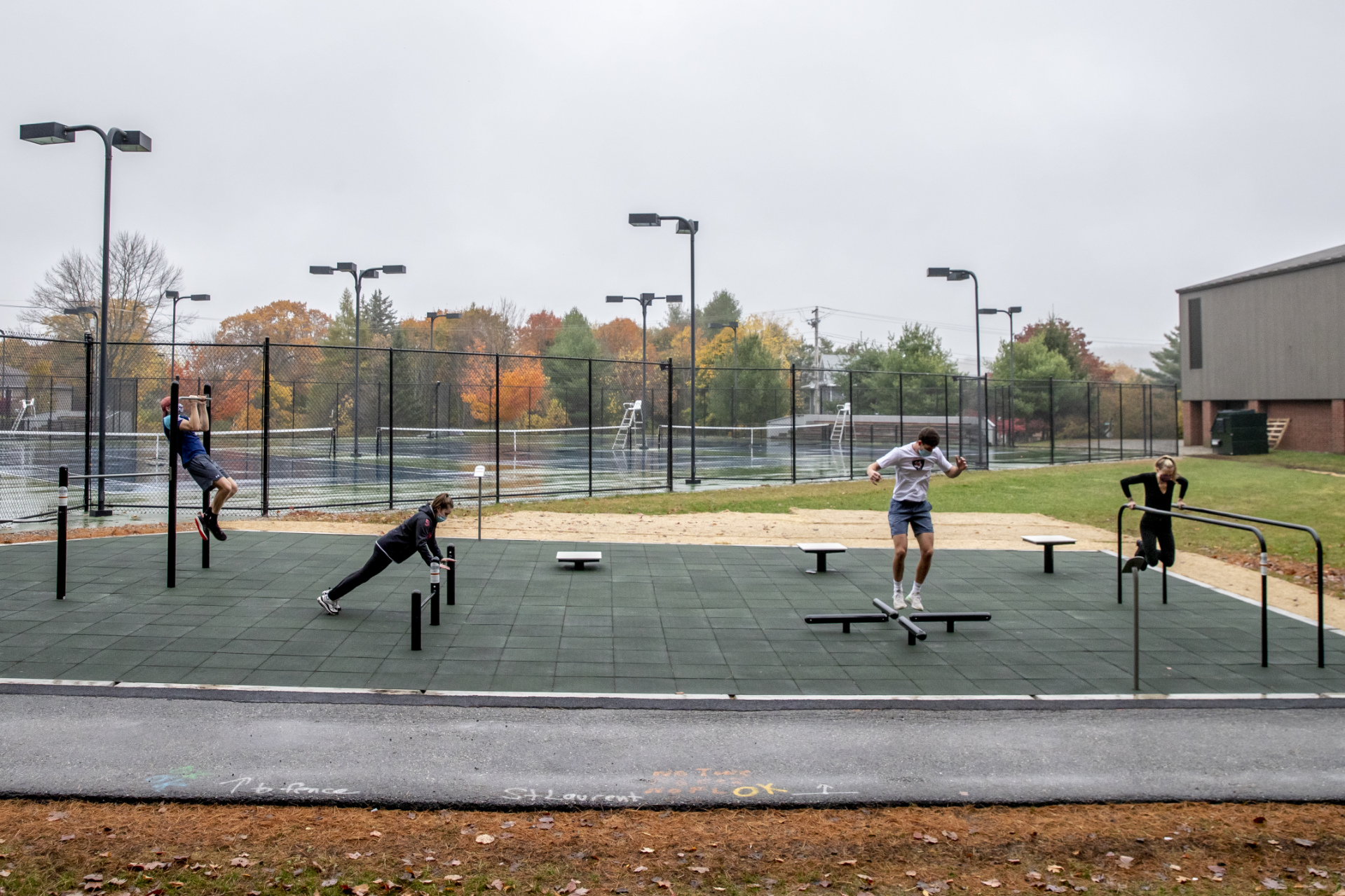 Each defying gravity in their own way, students work out at Bates' new fitness park on a damp October day. In the background is the Wallach Tennis Center. (Phyllis Graber Jensen/Bates College)