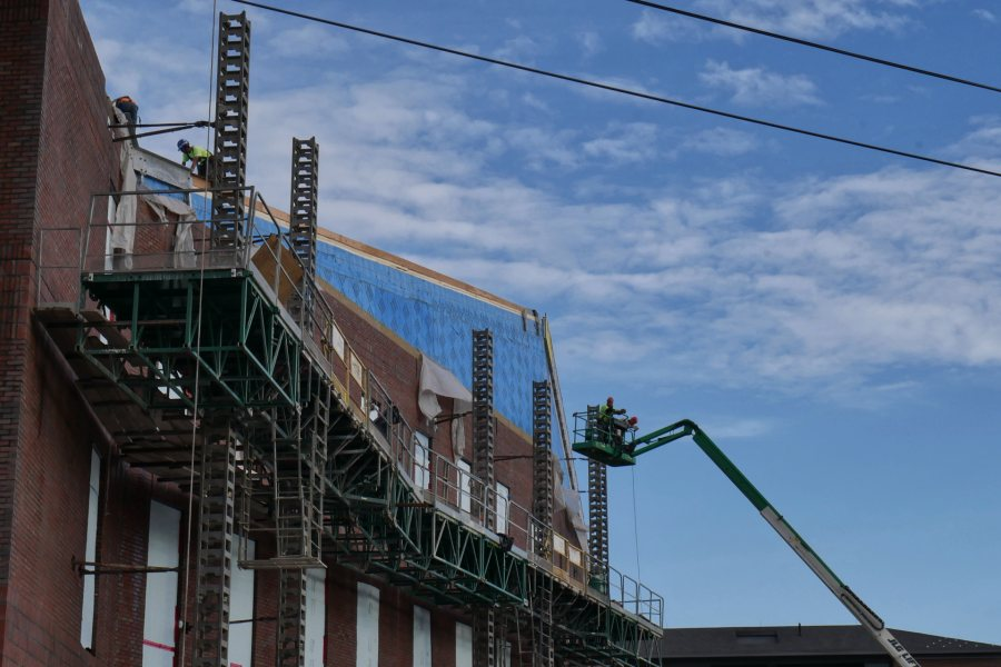 Masons and roofers at work on the south side of the science center on Oct. 22. (Doug Hubley/Bates College)